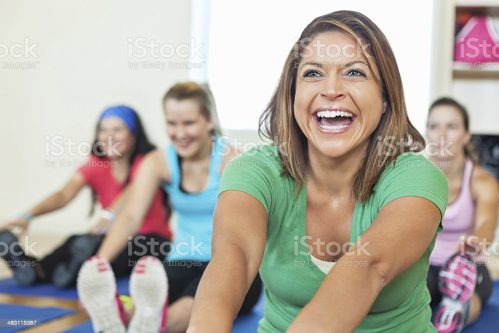 Smiling young woman stretching in fitness class royalty-free stock photo