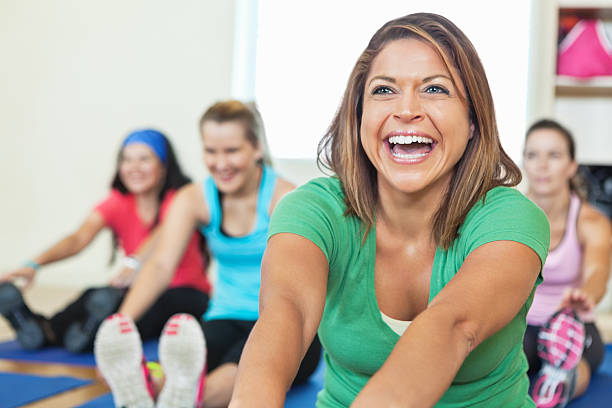 smiling young woman stretching in fitness class - gym skratt bildbanksfoton och bilder
