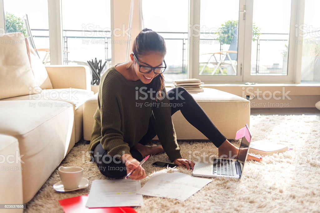 smiling young woman studying in her living room stock photo