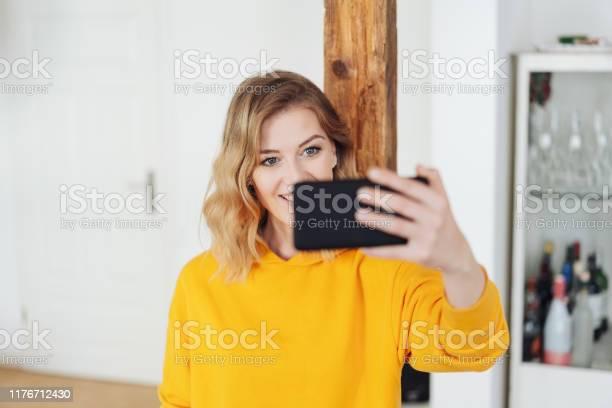 Smiling young woman taking a selfie at home picture id1176712430?b=1&k=6&m=1176712430&s=612x612&h=as9ch5iyyqdksh5sepmeq4nnshzzg n8hb3a82n1fbi=