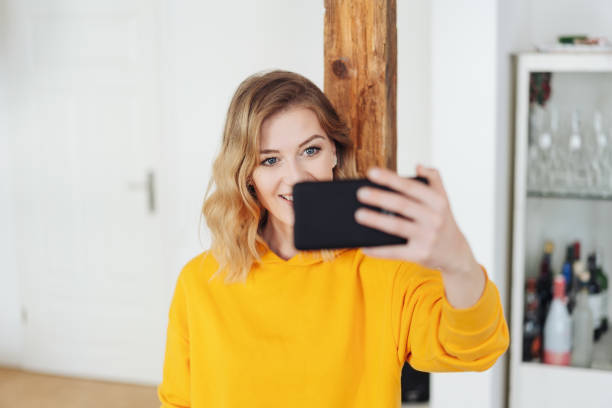 Smiling young woman taking a selfie at home stock photo