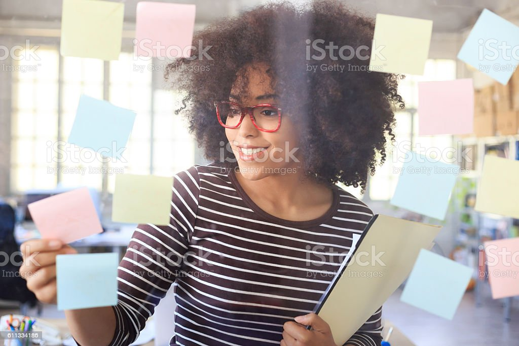 Smiling young woman taking colorful reminders from glass wall stock photo