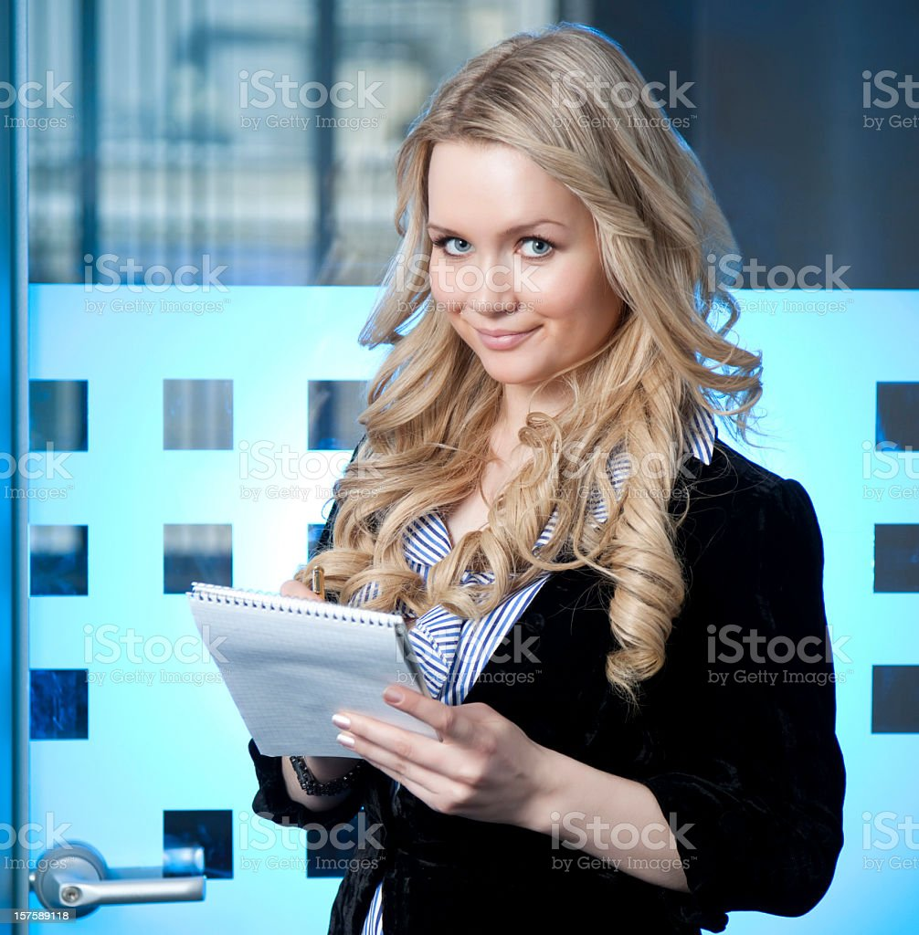 Smiling young woman taking notes royalty-free stock photo