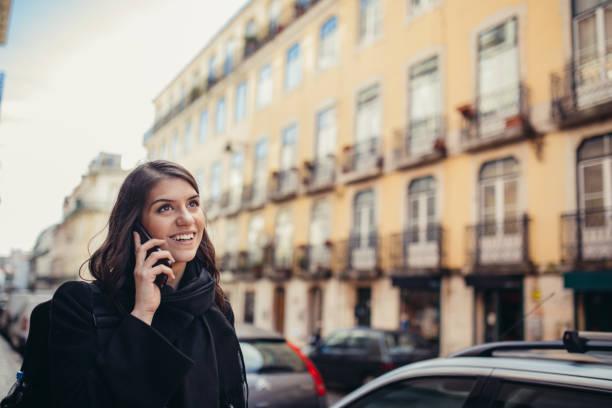 lächelnde junge frau auf ihrem smartphone auf den street.communicating im gespräch mit freunden, kostenlose anrufe und nachrichten für junge leute - iphone gratis stock-fotos und bilder