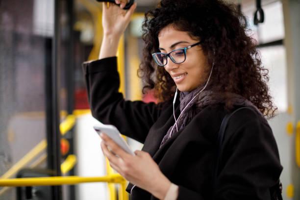lächelnde junge frau reisen mit dem bus und mit smartphone - bahn bus stock-fotos und bilder