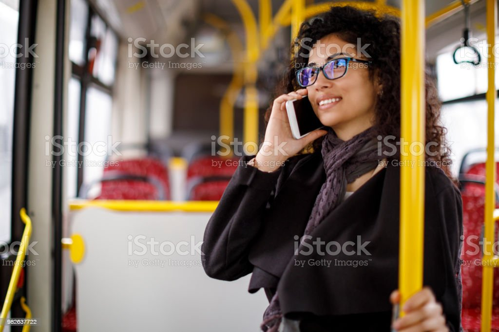 Smiling young woman traveling by bus and using smart phone stock photo