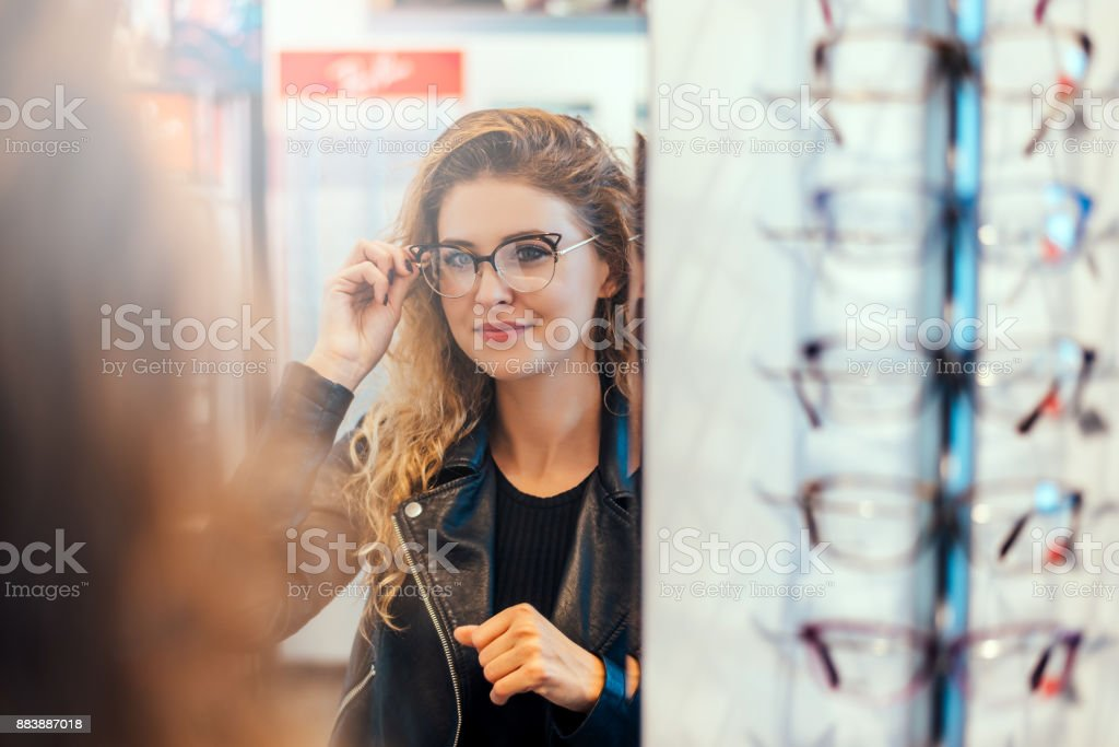 Smiling young woman trying on glasses on mirror in optician. stock photo