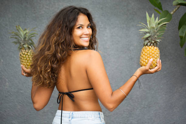 Smiling Young Woman Turning Back With Pineapples stock photo