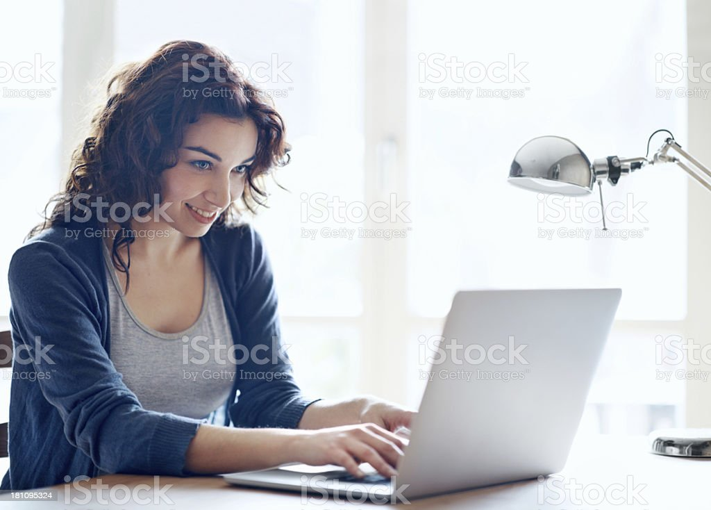 A smiling young woman using a laptop computer stock photo