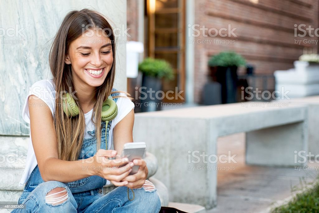 Smiling Young Woman Using a Smartphone stock photo