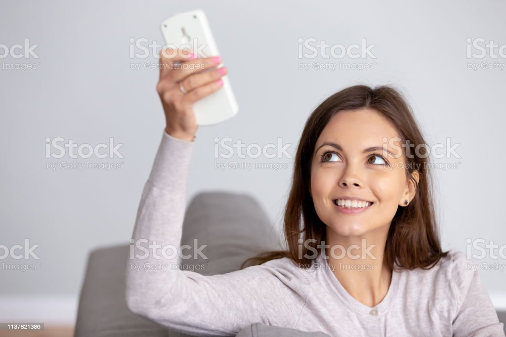 Smiling young woman using air conditioner remote controller close up stock photo