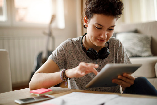 Smiling young woman using digital tablet at home