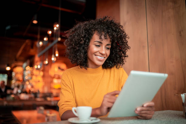Smiling young woman using digital tablet stock photo