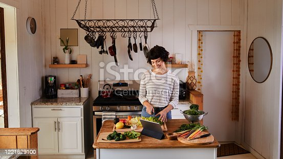 Smiling woman standing at an island in her kitchen at home chopping an assortment of fresh vegetables for a healthy meal