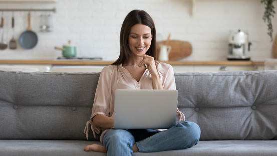 Smiling young woman using laptop, sitting on couch at home, beautiful girl shopping or chatting online in social network, having fun, watching movie, freelancer working on computer project