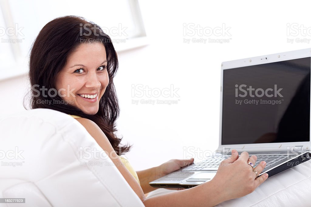 Smiling young woman using laptop, working at home royalty-free stock photo