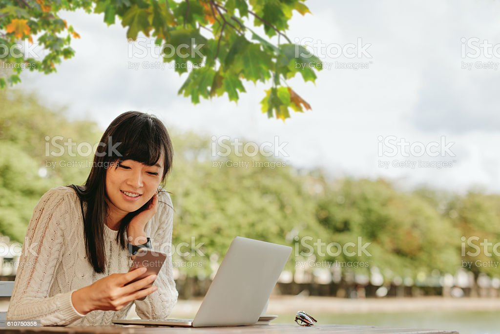 Smiling young woman using mobile phone at outdoor cafe. stock photo