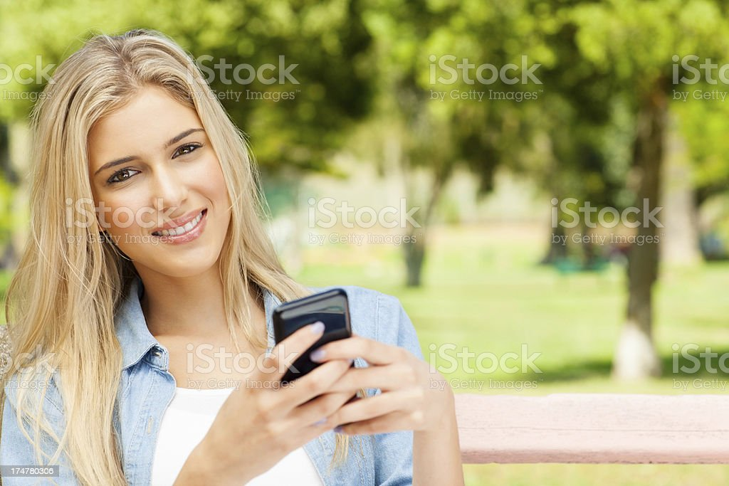 Smiling Young Woman Using Mobile Phone At Park. royalty-free stock photo