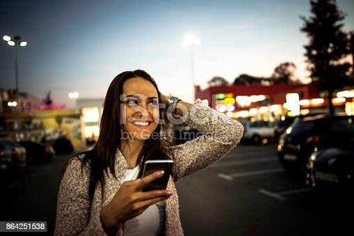 istock Smiling young woman using smart phone on streets by night 864251538