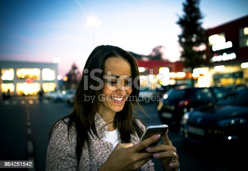 istock Smiling young woman using smart phone on streets by night 864251542