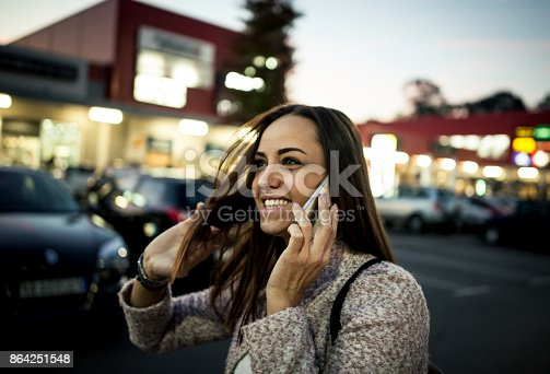 istock Smiling young woman using smart phone on streets by night 864251548