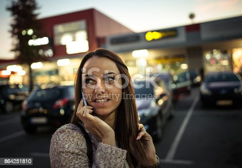 istock Smiling young woman using smart phone on streets by night 864251810