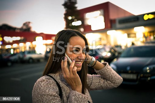 istock Smiling young woman using smart phone on streets by night 864251908