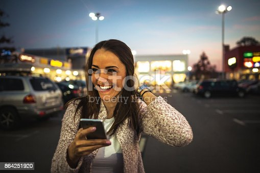 istock Smiling young woman using smart phone on streets by night 864251920