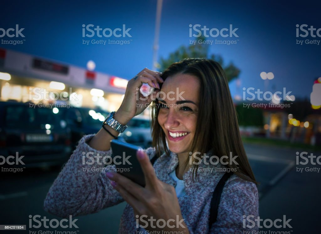 Smiling young woman using smart phone on streets by night royalty-free stock photo