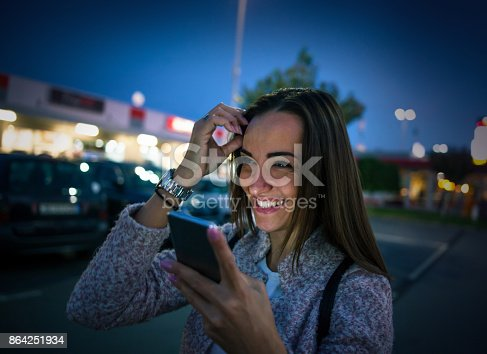 istock Smiling young woman using smart phone on streets by night 864251934