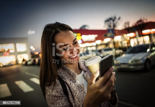 istock Smiling young woman using smart phone on streets by night 864252256