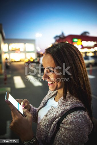 istock Smiling young woman using smart phone on streets by night 864252276
