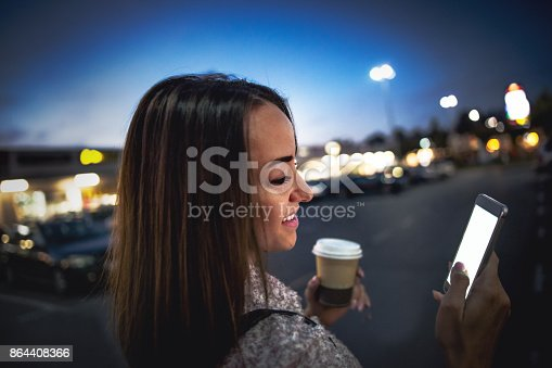istock Smiling young woman using smart phone on streets by night 864408366