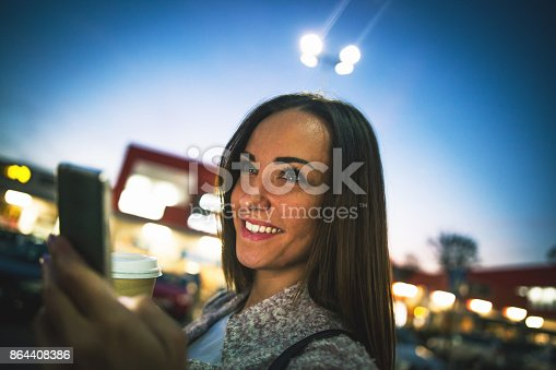 istock Smiling young woman using smart phone on streets by night 864408386
