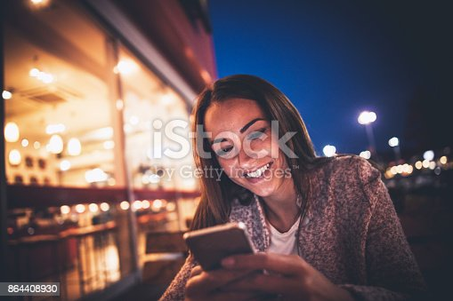 istock Smiling young woman using smart phone on streets by night 864408930