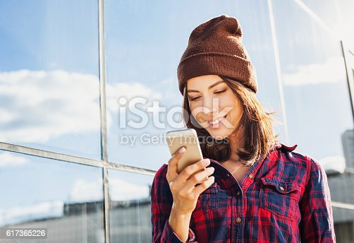 518885222istockphoto Smiling young woman using smart phone 617365226