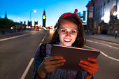 Smiling young woman using digital tablet on street at night.
