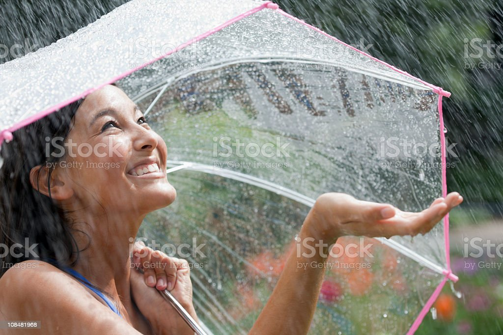 Smiling young woman using umbrella in rain stock photo