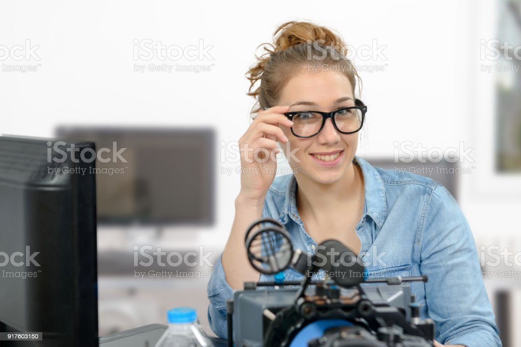 smiling young woman video editing in office stock photo
