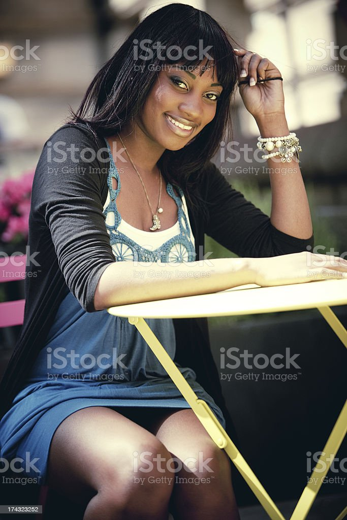 Smiling Young Woman waiting to be served in street cafe royalty-free stock photo