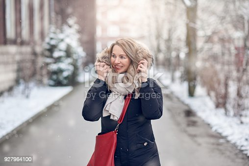 Smiling young woman walking along a snowy road in winter holding the fur trim on her jacket looking to the side with a happy smile