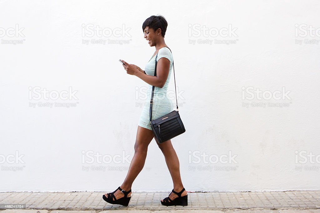 Smiling young woman walking and looking at cell phone stock photo