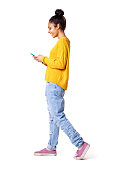 istock Smiling young woman walking and looking at mobile phone 539464476
