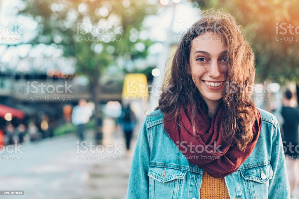 Smiling young woman walking on the street stock photo