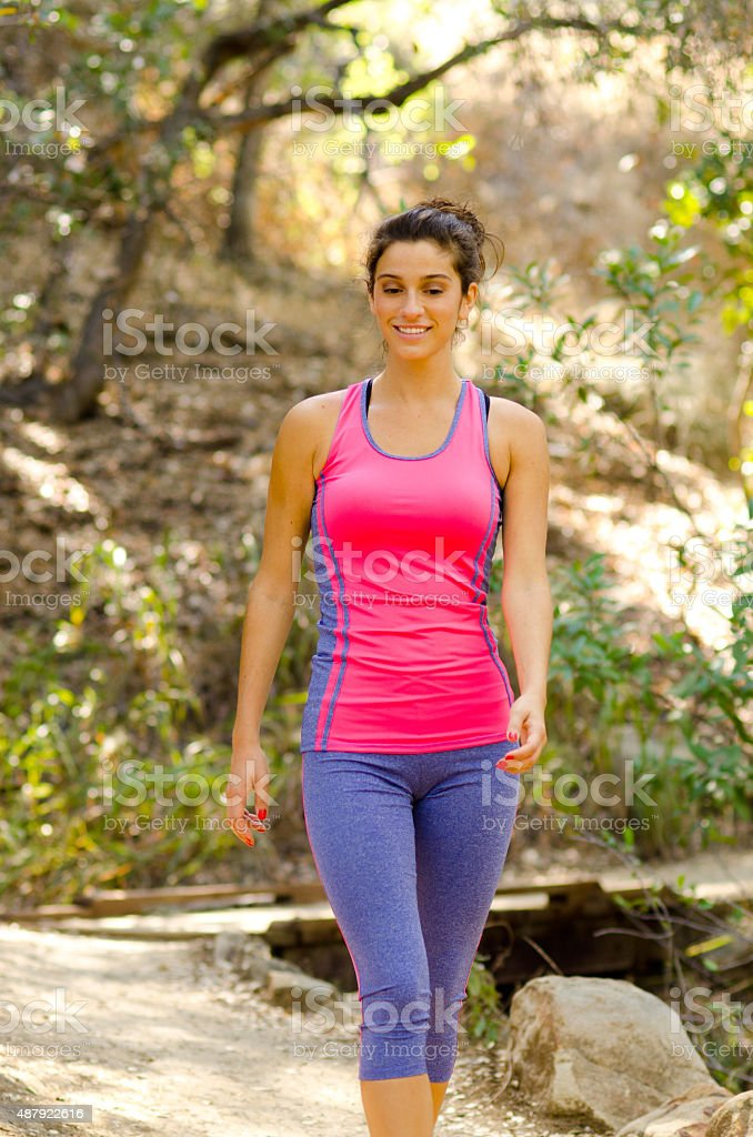 Smiling young woman walking stock photo