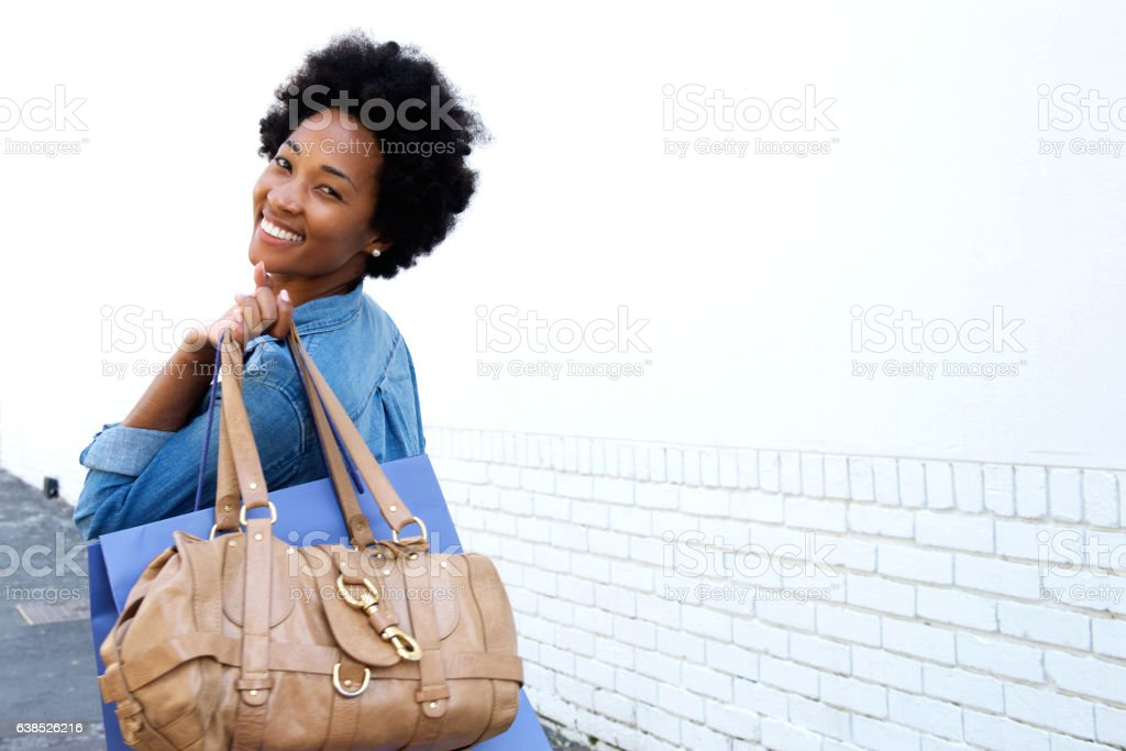 Smiling young woman walking with bags stock photo