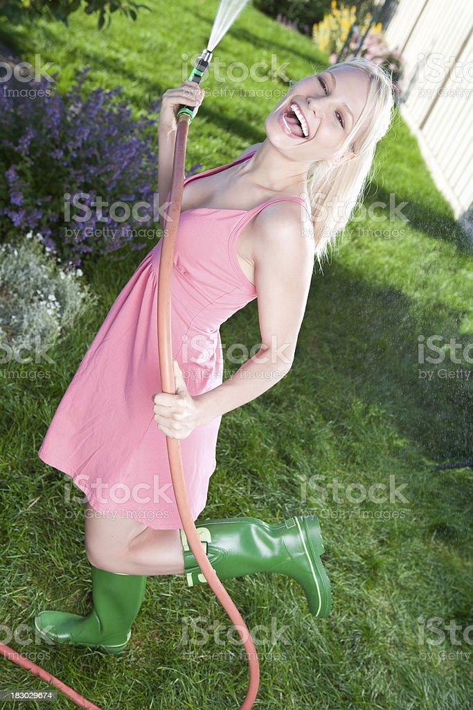 Smiling young woman watering garden royalty-free stock photo