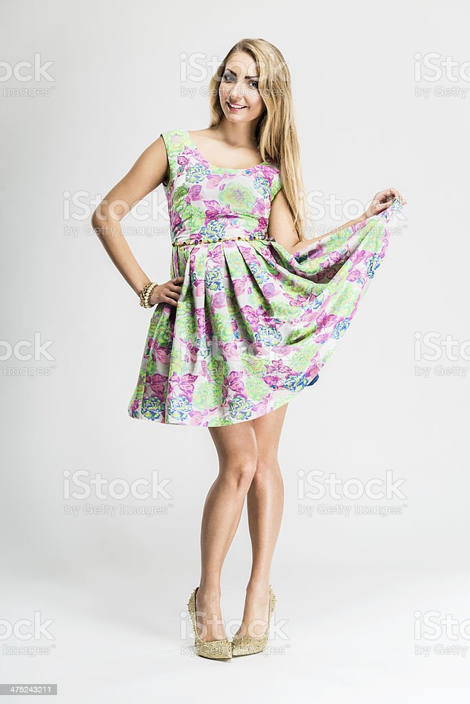 Smiling young woman wearing fashionable sleeveless dress with floral design stock photo