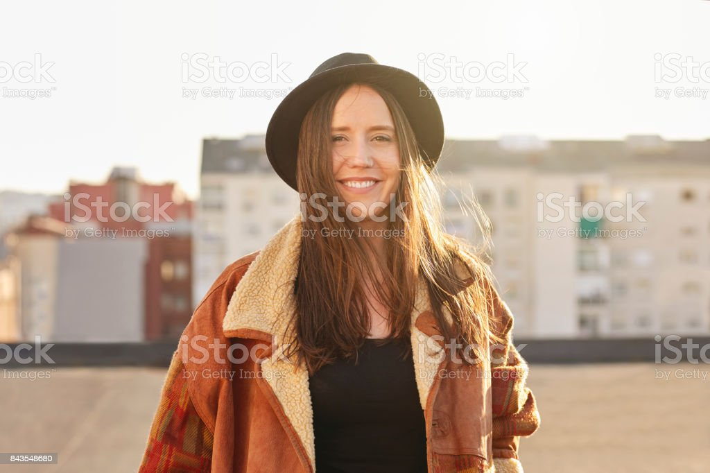Smiling young woman wearing hat and jacket stock photo