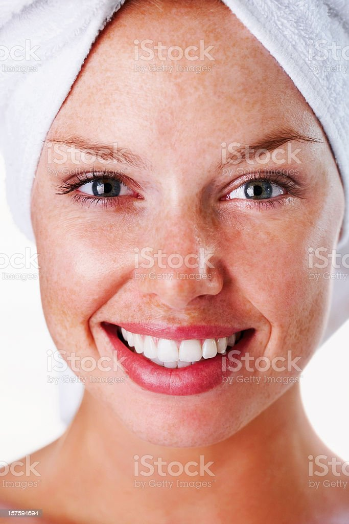 Smiling young woman with a towel wrapped on head royalty-free stock photo